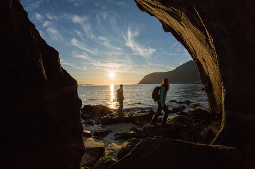 A couple watching the sunset by the water in the Forillon National Park