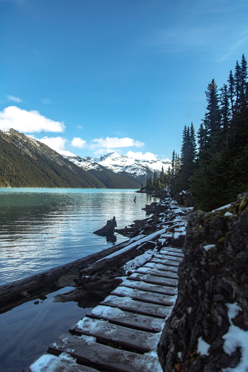 A snowy trail by the Garibaldi lake with the impressive mountains in the background