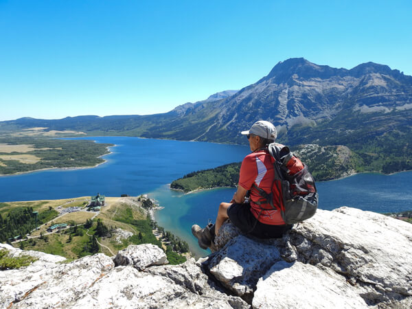 A man wearing LOWA Camino GTX boots looking at the view over the Waterton Lakes National Park