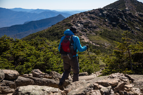 A man wearing his LOWA Camino GTX boots with LEKI hiking poles going up the Franconia Ridge Trail on Mount Lafeyette