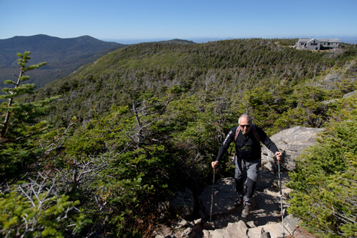 A man hiking up the Franconia Ridge Trail on Mount Lafayette. You can see a mountain hut in the background.