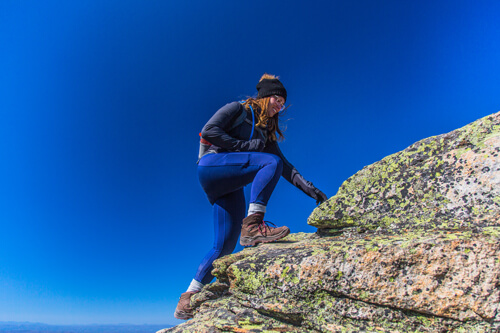 A girl wearing her LOWA Renegade GTX WS boots while hiking up Mount Lafette in New Hampshire during fall