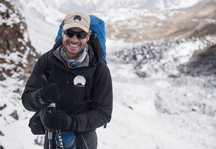 Emmanuel Daigle smiling at the camera while hiking in the Himalaya's
