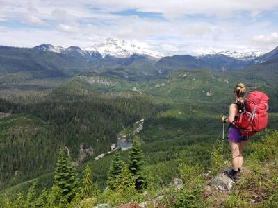Kristine of Hikes Near Vancouver portant un sac à dos Vaude de 60 litres au bord d'une falaise surplombant une vallée en Colombie-Britannique.