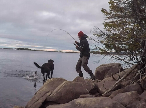 Justin Barbour, The Newfoundland explorer, catching a fish while his dog Saku await for dinner