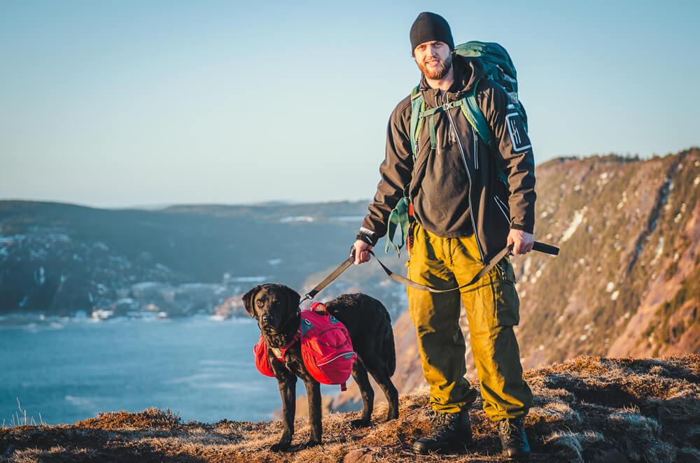 Portrait shot of Justin Barbour with his dog Saku hiking in Labrador, Newfoundland.