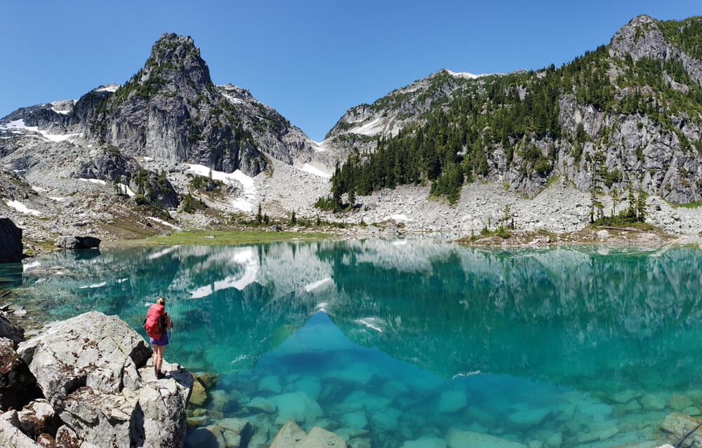 Kristine Krynitzki from Hikes Near Vancouver overlooking a beautiful cyan lake with mountains in the background