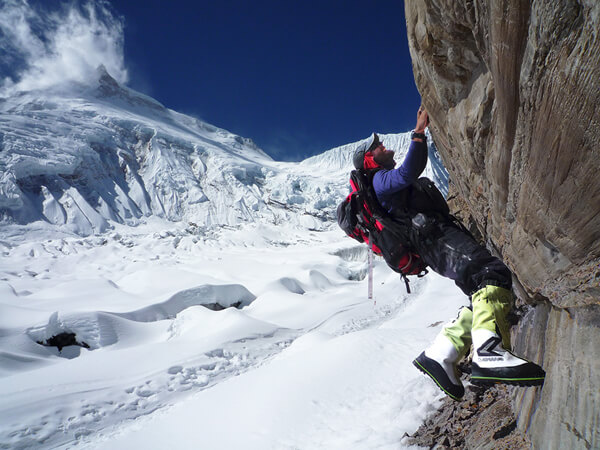 Emmanuel Daigle of the Haute Montagne Academy climbing a rock formation with his LOWA Alpine boots