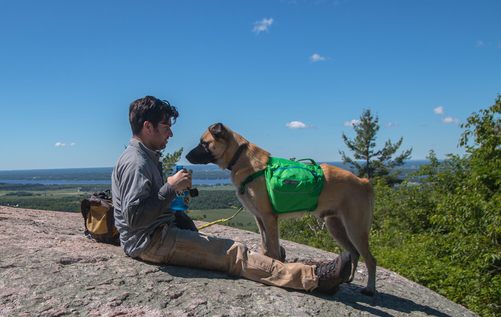 Dean Campbell en pause et entrain de boire de l'eau avec son chien pendant une randonnée.