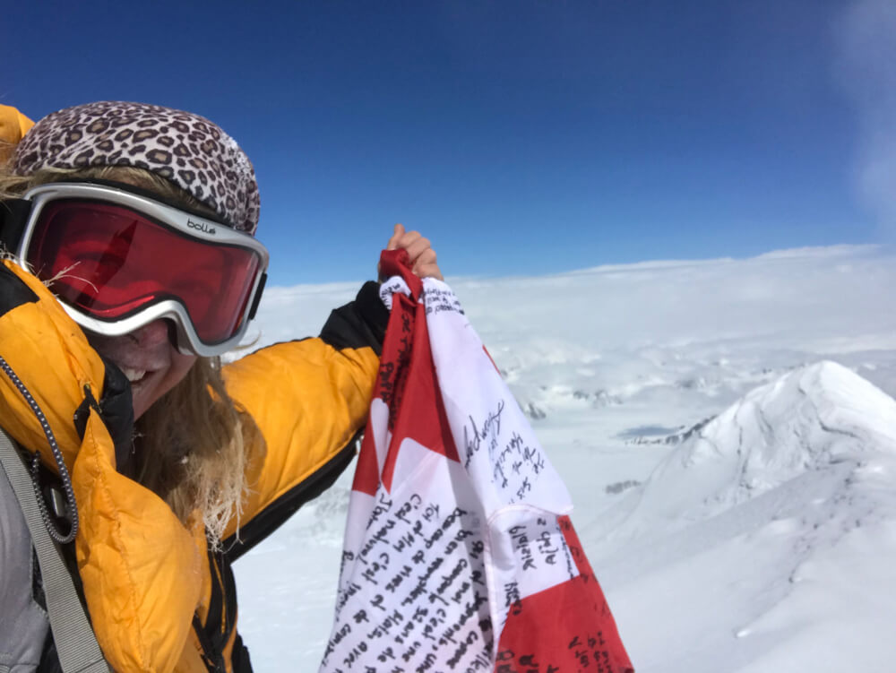The Canadian alpinist Monique Richard proudly taking a selfie on top of Mount Logan with the Canadian flag